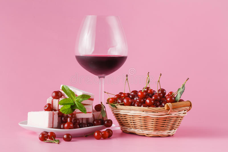 Cherry homemade liquor in a glasses on pink background and cherries stock photos