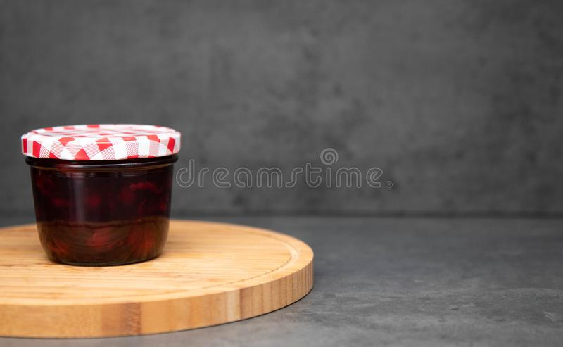 Cherry jam in a glass jar with a closed red and white lid on a wooden plate. Gray background. Cherry jelly in a jar on a wooden royalty free stock photo