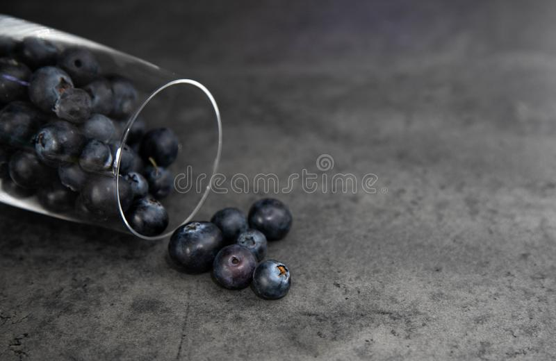 Cherry jam in a glass jar with an open lid of red and white color on a wooden board, a board. Gray background. Place for text stock photo