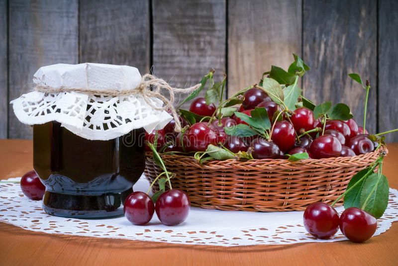 Cherry jam jar and fresh cherries stock image