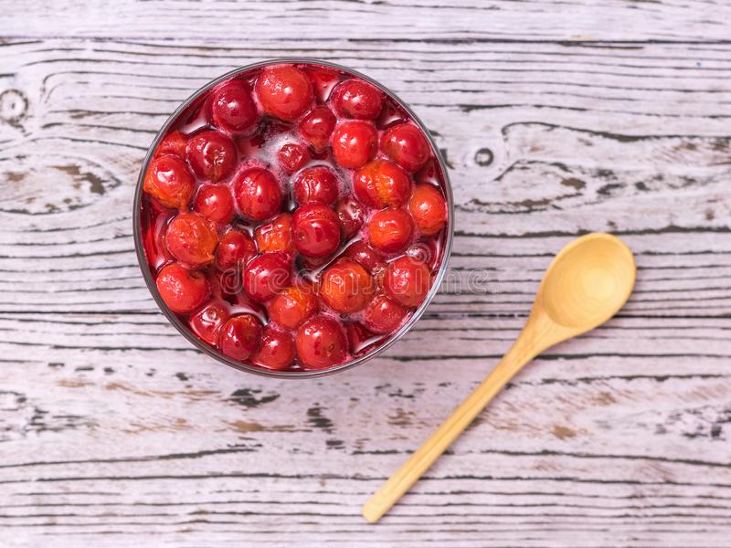 Cherry jam and wooden spoon on wooden table. Homemade jam from the fresh harvest of cherry berries. Flat lay. Cherry jam and wooden spoon on wooden table stock photos