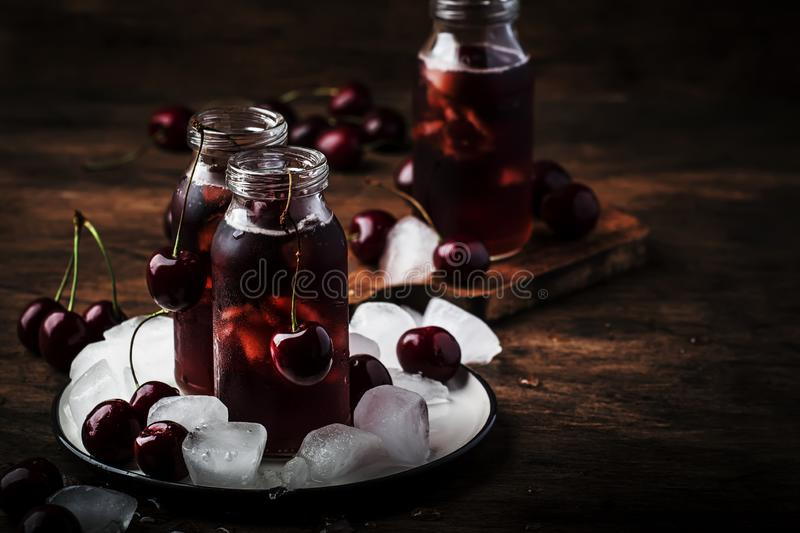 Cherry juice, cold beverage with ice in glass bottles on vintage wooden table, low key, copy space. Cherry juice, cold beverage with ice in glass bottles on royalty free stock images