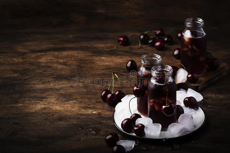 Cherry juice, cold beverage with ice in glass bottles on vintage wooden table, low key, copy space. Cherry juice, cold beverage with ice in glass bottles on stock photo
