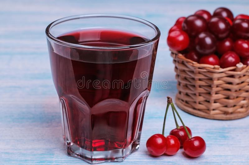Cherry juice in a glass next to a fresh cherry close-up on a blue wooden table stock image