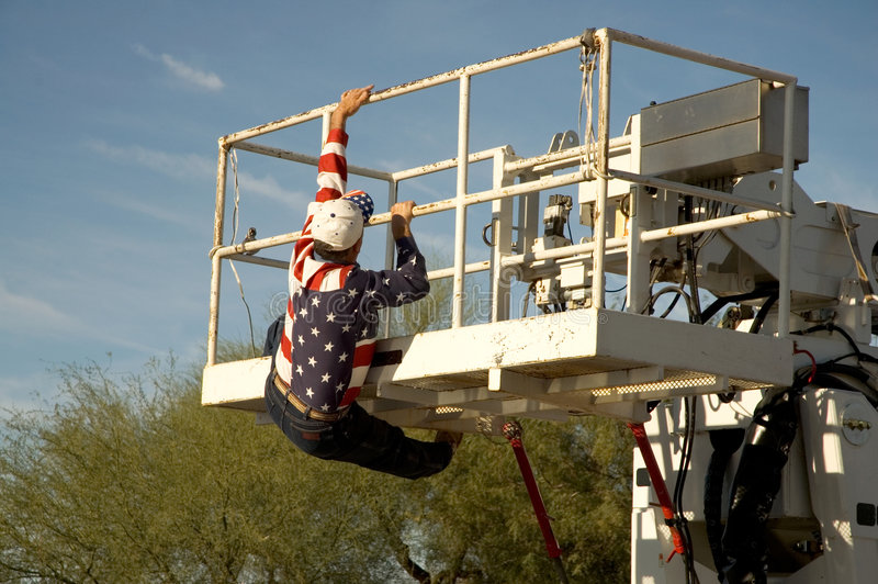 Cherry Picker. Workman in flag shirt climbing into the bucket of a cherry picker stock image