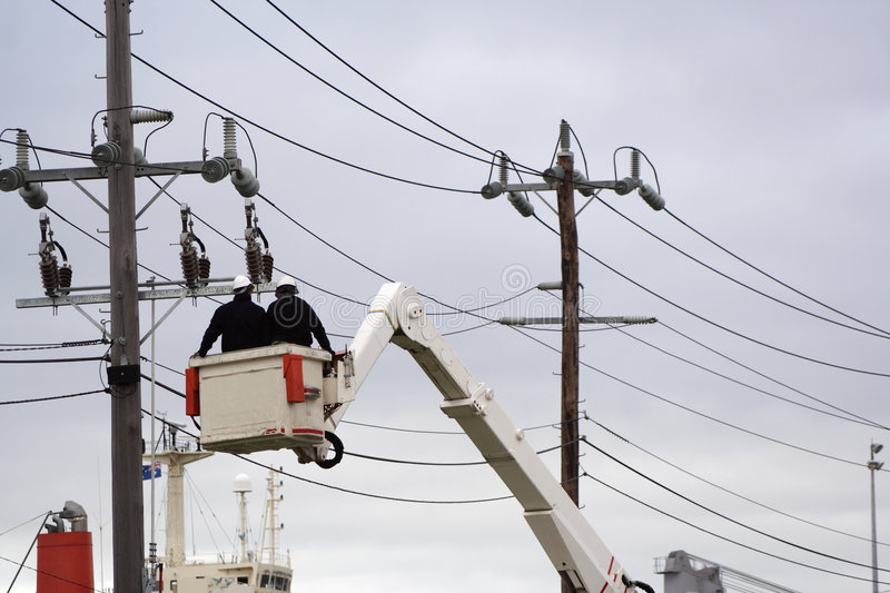 Cherry picker. Workers in cherry picker fixing power lines royalty free stock photo