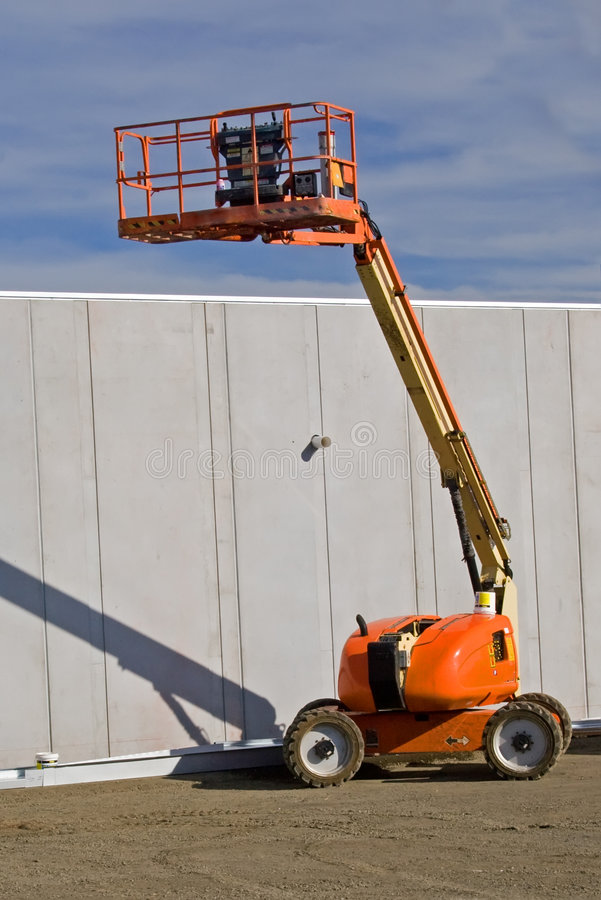 Cherry Picker. Elevated cherry picker on construction site stock photography