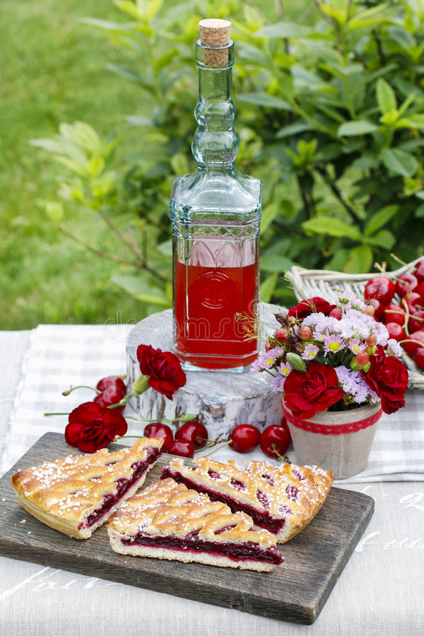 Cherry pie and cherry juice at the table. Cherry pie and cherry juice at the garden party table royalty free stock photos