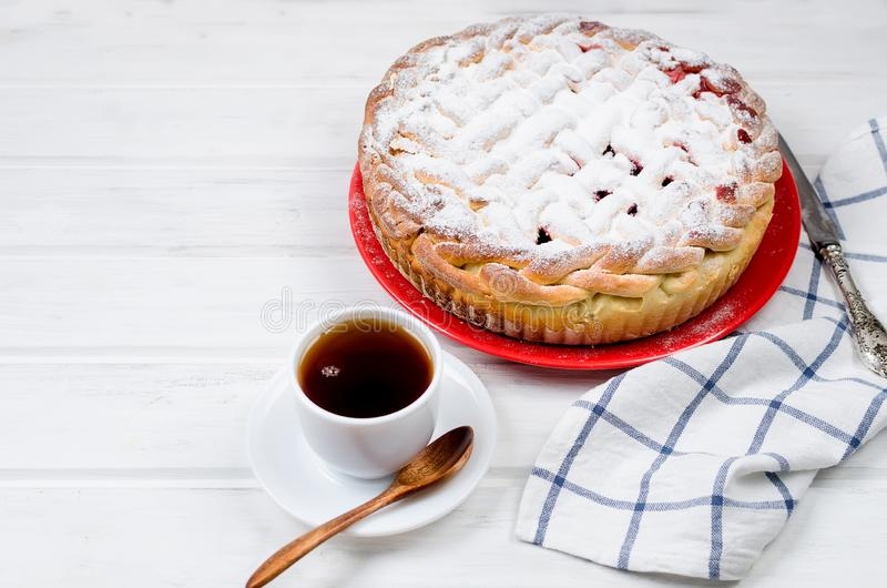 Cherry Pie in a glass round form, yeast cake. Delicious Homemade cherry Pie dusted with icing sugar on the plate whits cup of tea on the white old wooden table stock photography