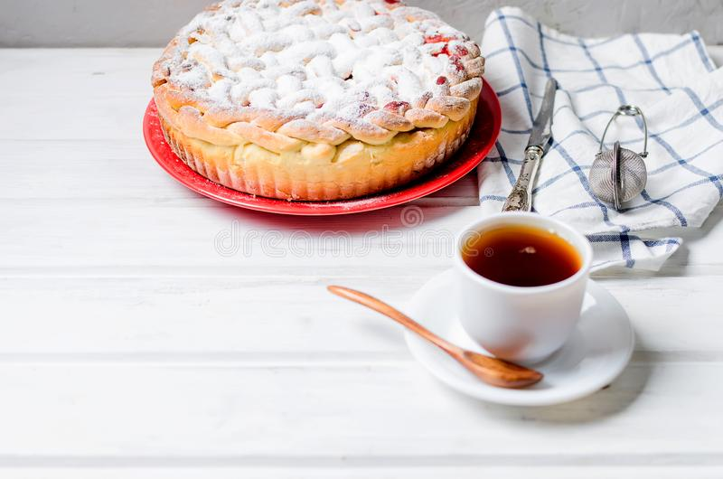 Cherry Pie in a glass round form, yeast cake. Delicious Homemade cherry Pie dusted with icing sugar on the plate whits cup of tea on the white old wooden table stock photos
