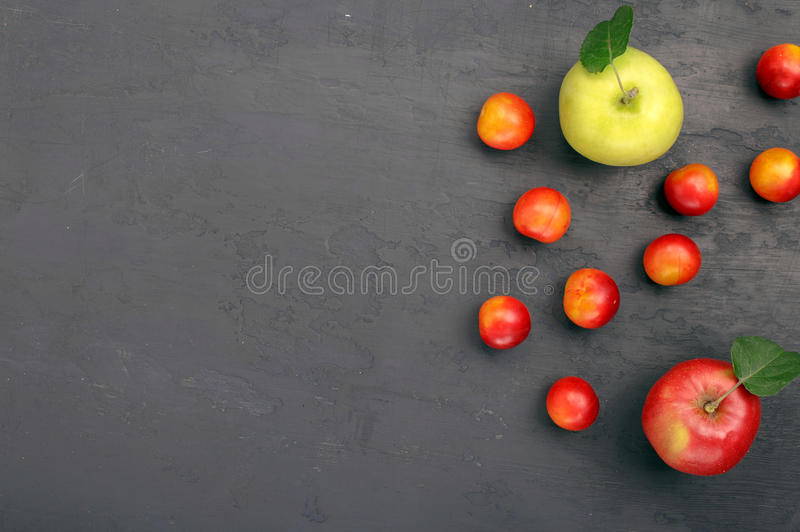 Cherry plum and apples. In dark rough background with copy space, top view royalty free stock photos