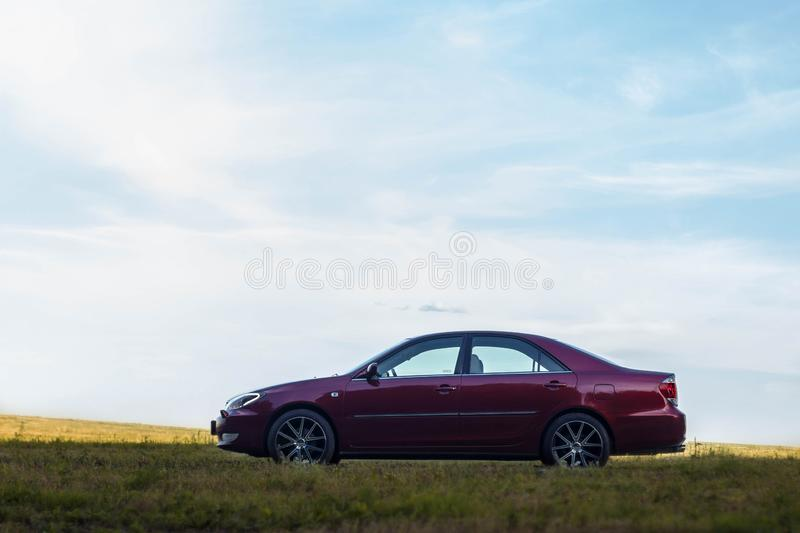 Cherry red 4 door family d-class sedan Toyota Camry. Fifth generation xv30 2001-2006 standing on a green field and forest on a background at the summer with led stock image