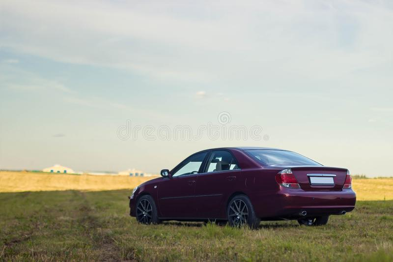 Cherry red 4 door family d-class sedan Toyota Camry. Fifth generation xv30 2001-2006 standing on a green field and forest on a background at the summer with led royalty free stock photos