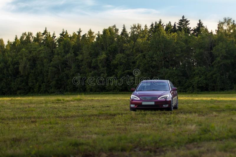 Cherry red 4 door family d-class sedan Toyota Camry. Fifth generation xv30 2001-2006 standing on a green field and forest on a background at the summer with led royalty free stock photo