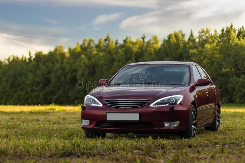 Cherry red 4 door family d-class sedan Toyota Camry. Fifth generation xv30 2001-2006 standing on a green field and forest on a background at the summer with led royalty free stock photography