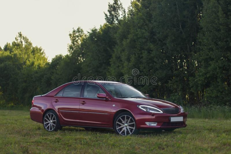 Cherry red 4 door family d-class sedan Toyota Camry. Fifth generation xv30 2001-2006 standing on a green field and forest on a background at the summer with led stock images