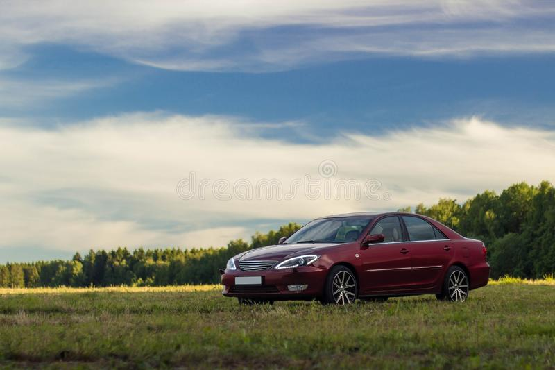 Cherry red 4 door family d-class sedan Toyota Camry stock photo