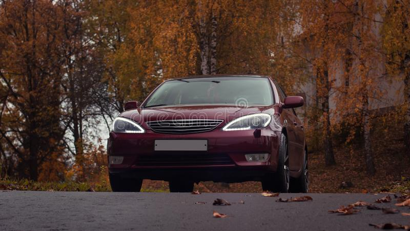 Autumn scene with Cherry red 4 door family d-class sedan Toyota Camry stock images
