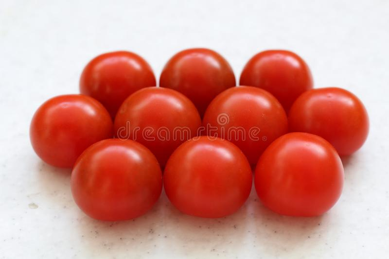 Cherry red tomatoes stack isolated on table royalty free stock photos