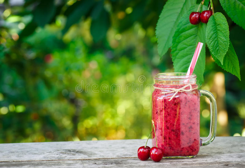 Cherry smoothie in mason jar. And fresh ripe cherries on wooden table with garden on the background. Healthy summer drink concept. Berry cocktail stock images