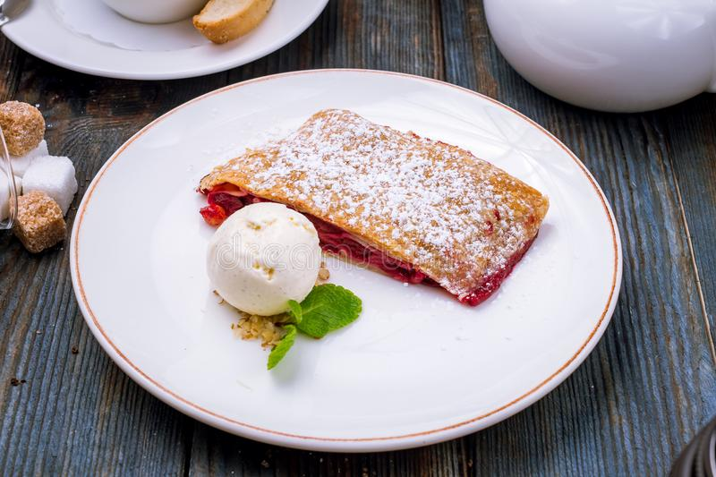 Cherry strudel with ice cream. On a white plate stock image