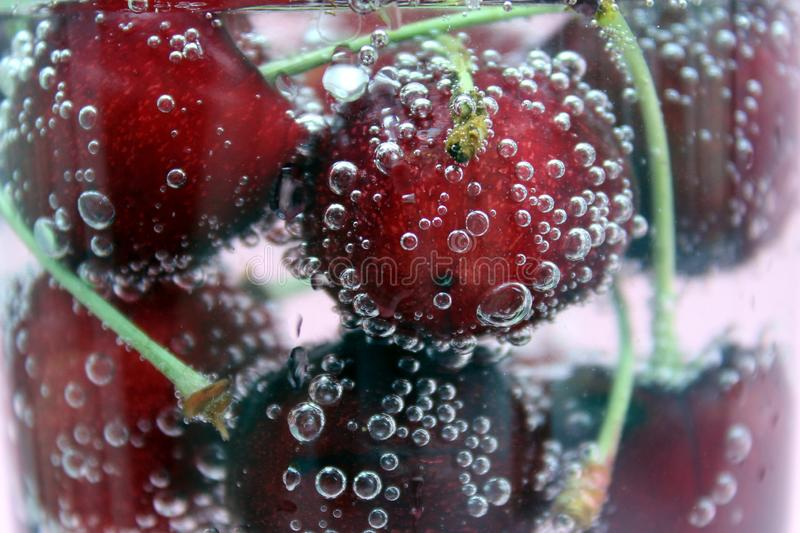 Bright red fresh cherry floats in sparkling water in a glass and covered with bubbles. Cherry, sweet cherry, bright, bubbles, bubbling, aerated, cling, cold stock photography