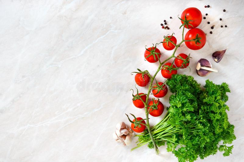 Cherry tomato branch, garlic, fresh parsley, pepper on a light background. royalty free stock image