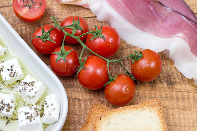 Cherry tomato, cheese in olive oil with basil, toasted bead and prosciutto on wooden background royalty free stock photos
