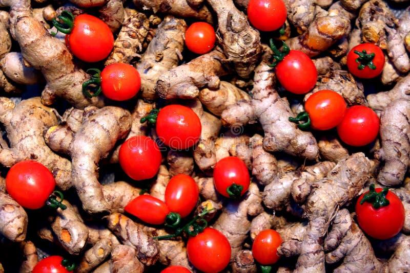 Cherry Tomato-Hintergrund mit Gelbwurz lizenzfreie stockbilder