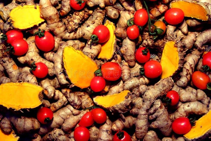 Cherry Tomato-Hintergrund mit Gelbwurz stockbild