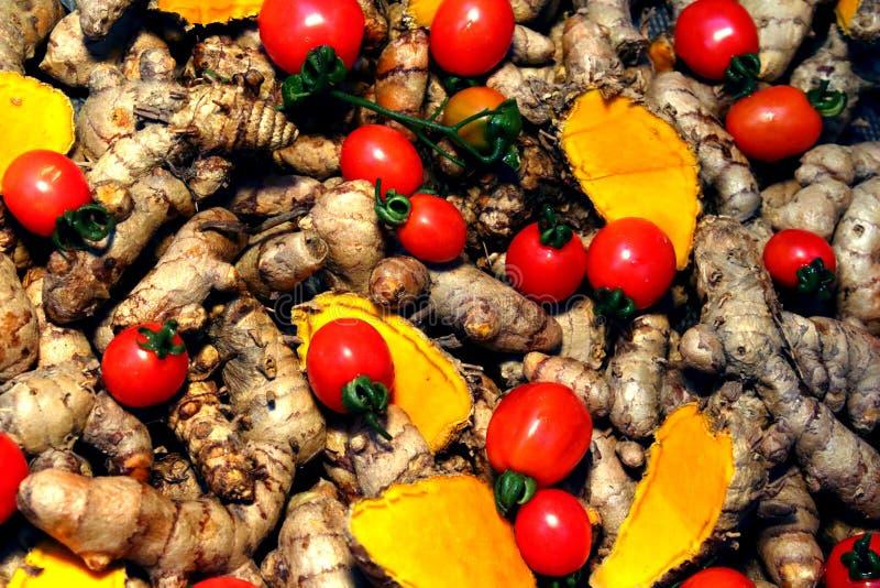 Cherry Tomato-Hintergrund mit Gelbwurz lizenzfreie stockfotos