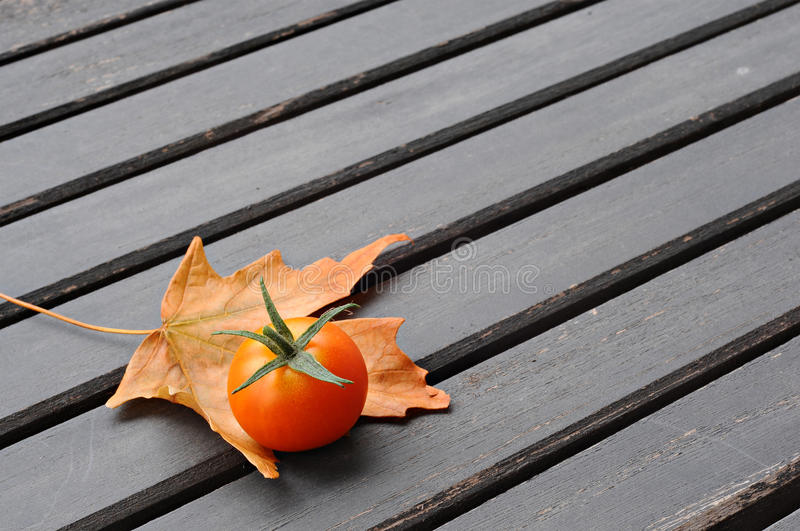 Cherry tomato and a leaf, on a wooden table royalty free stock images