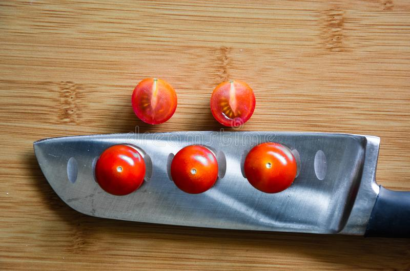 Cherry tomatoes over kitchen knife stock photos