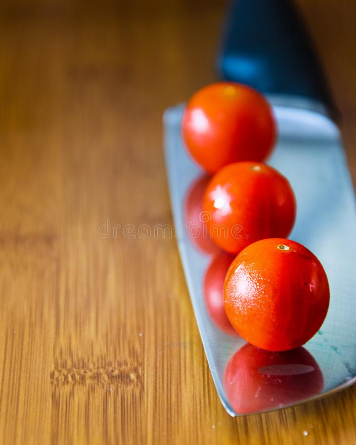 Cherry tomatoes over kitchen knife stock image