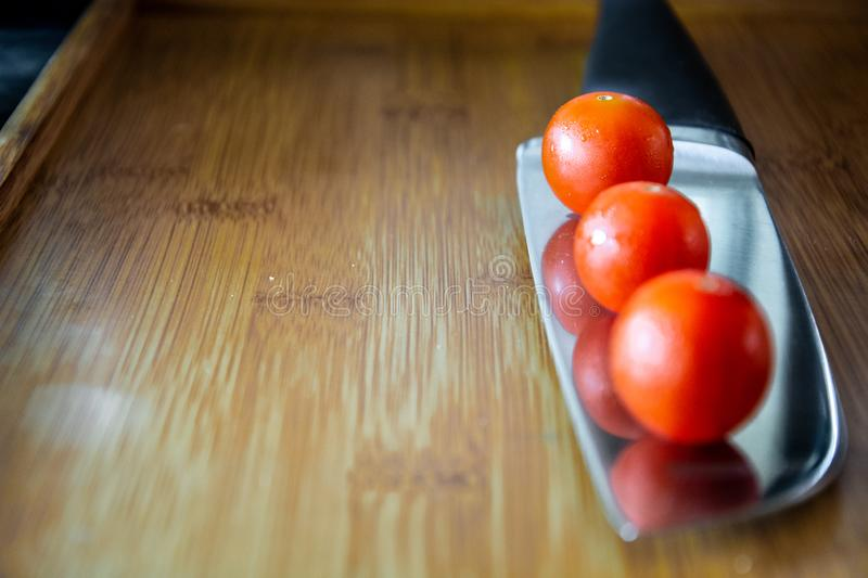 Cherry tomatoes over kitchen knife royalty free stock image
