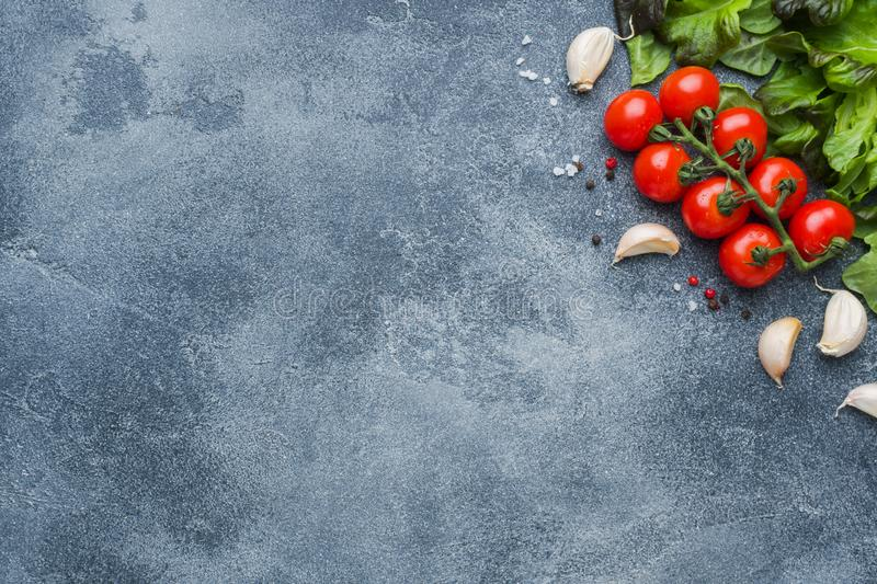Cherry tomatoes on a branch Fresh herbs and garlic clove with spices on a dark stone table. Top view with copy space. Cherry tomatoes on a branch Fresh herbs and stock photos
