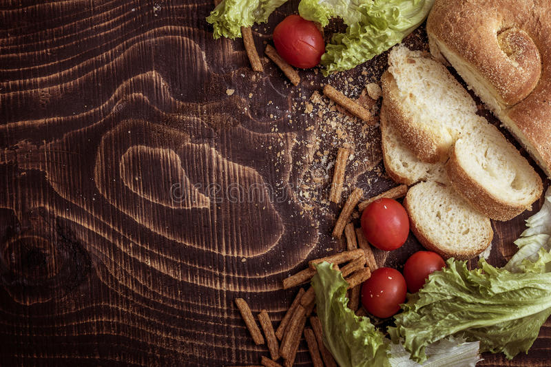 Cherry tomatoes. bread, sausage, lettuce. On a wooden brown background basket of products, the stick of sausage, lettuce, cherry tomatoes, homemade bread round stock photography