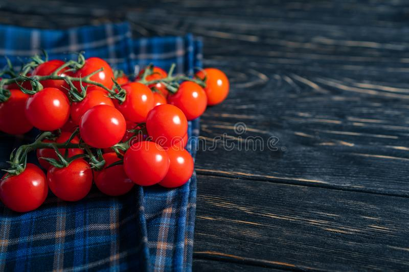 Cherry tomatoes in the checkered cloth serviette on the wooden table. Cherry tomatoes in the checkered cloth serviette on the dark wooden table. Juicy ripe royalty free stock photography