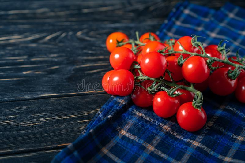 Cherry tomatoes in the checkered cloth serviette on the wooden table. Cherry tomatoes in the checkered cloth serviette on the dark wooden table. Juicy ripe royalty free stock photo