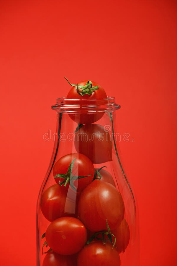 Cherry tomatoes in glass bottle over red stock images