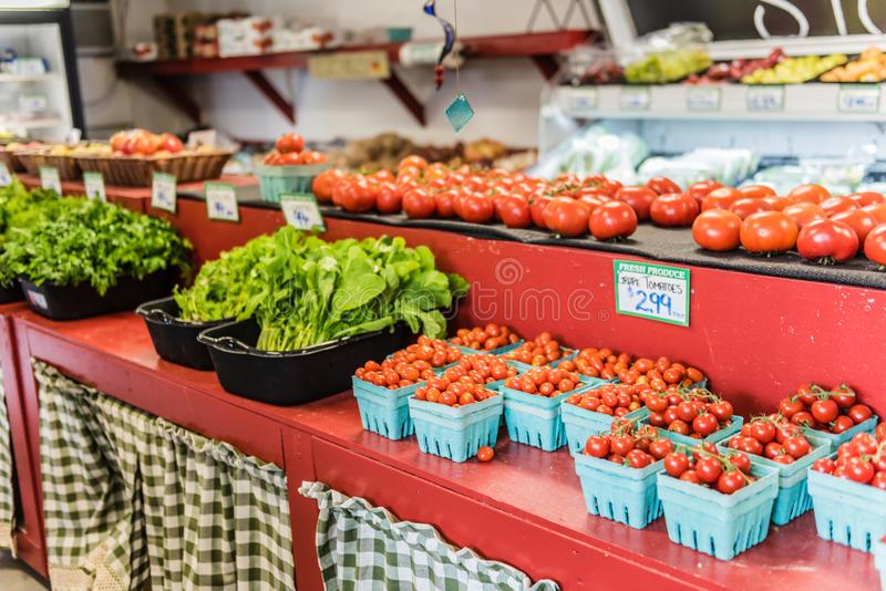 Cherry Tomatoes At Hudson Valley Country Store. Cherry Tomatoes and other vegetables on shelves at country grocer in Hudson Valley, New York stock photo