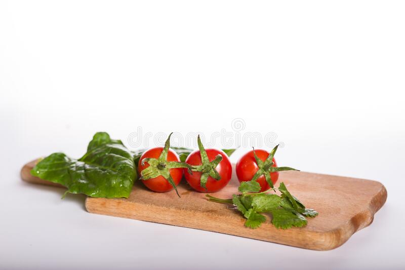 Cherry tomatoes on a kitchen board. Healthy eating basics royalty free stock image