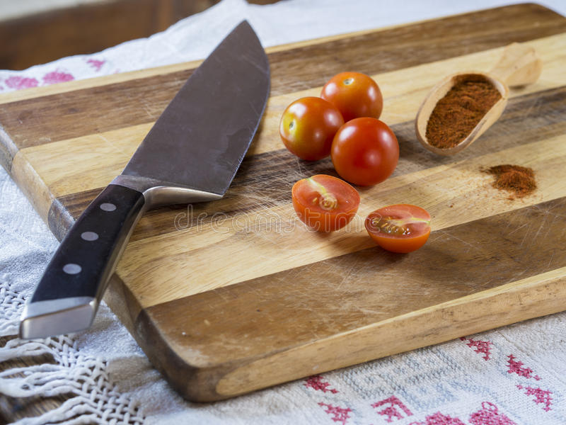 cherry tomatoes with kitchen knife and scoop with red pepper spice on wooden cutting board royalty free stock image