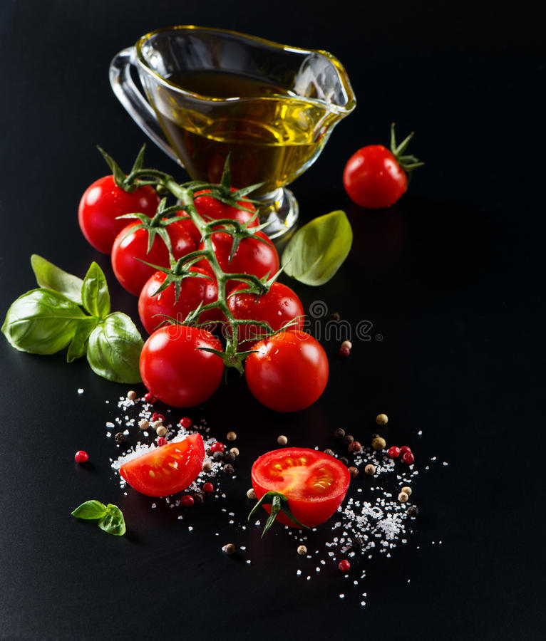 Cherry tomatoes, olive oil and basil. Basil, tomatoes, olive oil, pepper, garlic and salt. Ingredients for Italian food on a black background stock image