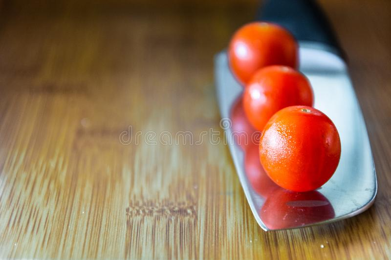 Cherry tomatoes over kitchen knife royalty free stock photos