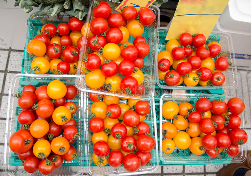 Cherry tomatoes in plastic boxes stock photography