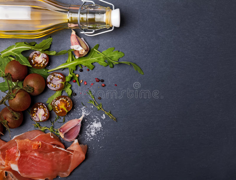 Cherry tomatoes, prosciutto, arugula and spices royalty free stock photo