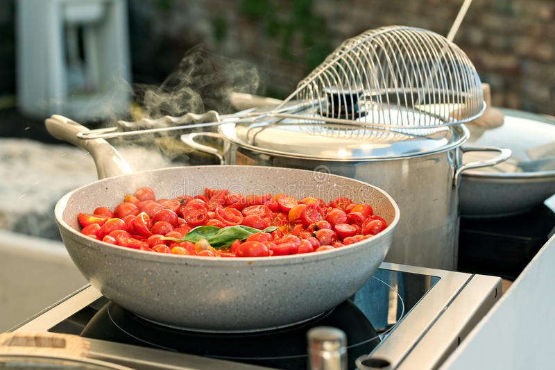 Cherry tomatoes on a saucepan. Sliced cherry tomatoes with basil cooking on a saucepan stock image