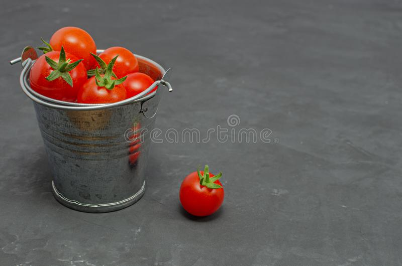 Cherry tomatoes in a toy mini decorative bucket on a dark background. Beautiful still Life. Top view with copy space. Healthy nutrition. Selective focus stock image