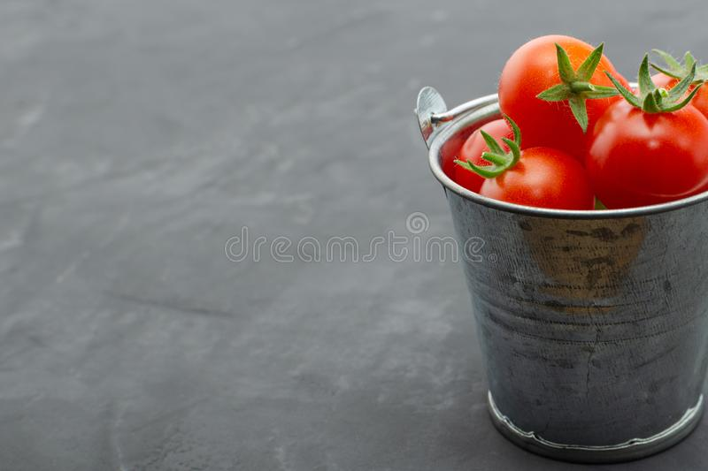 Cherry tomatoes in a toy mini decorative tin bucket on a dark background. Beautiful still Life. Top view with copy space. Healthy nutrition. Selective focus royalty free stock photos